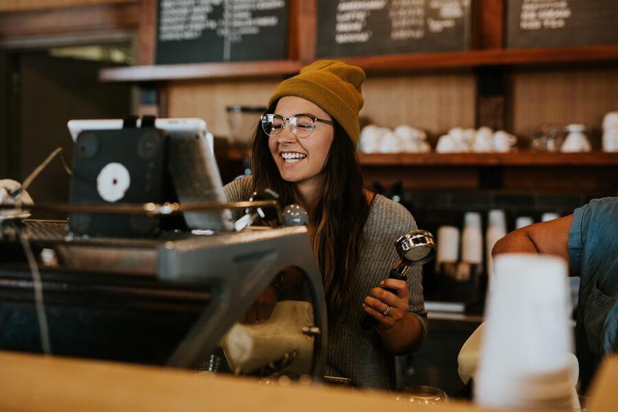 Smiling barista making espresso.