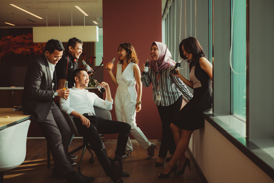 Business people laughing together while sharing a beverage.